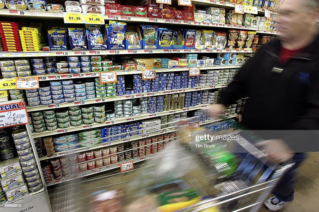 A shopper walks by cans of tuna fish on display in a grocery store January 27 2006 in Des Plaines Illinois New data released by the Food and Drug...