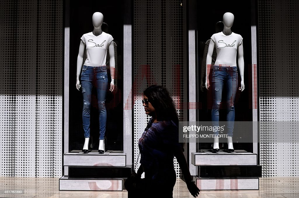 A shopper walks by shop windows advertising sale, in downtown Rome, on July 6, 2014 as the Summer sale starts at Italian retailers.