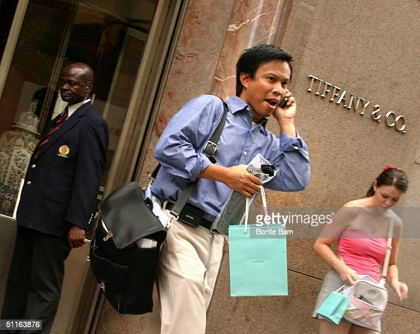 A shopper walks out of the storefront of Tiffany Co August 12 2004 in New York City The luxury jeweler announced August 12 that quarterly profit fell...