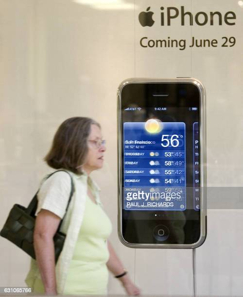 A shopper walks past a display for the new Apple IPhone in the Tysons Corner Mall in McLean Virginia 26 June 2007 The 29 June release of Apple's...