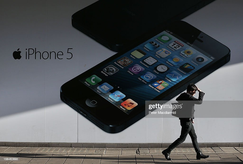 A shopper walks past a giant advertisment for the Apple iPhone 5 near Oxford Street on December 17, 2012 in London, England. Thousands of shoppers are expected in London's west end in the hunt for Christmas bargains in the next week.
