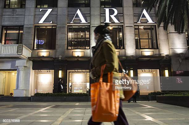 A shopper walks past a Zara store operated by Inditex SA in Shanghai China on Monday Dec 21 2015 China will add monetary stimulus next year making...