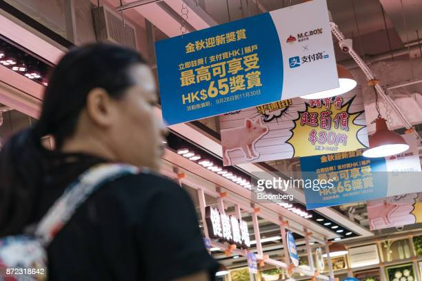 A shopper walks past advertisement banners for for Ant Financial Services Group's Alipay an affiliate of Alibaba Group Holding Ltd left and second...