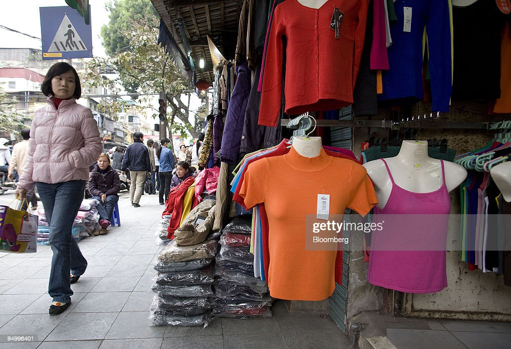 A shopper walks past clothing displayed for sale in Hanoi Vietnam on Sunday Dec 20 2009 Vietnam's fourthquarter GDP figures will be released on or...