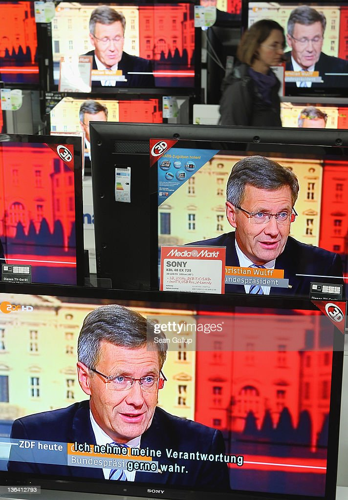 A shopper walks past flat-screen televisions showing an interview with German President Christian Wulff in which he was scheduled to respond to critics on the 7pm news at an electronics store on January 4, 2011 in Berlin, Germany. Wulff has come under increasing pressure to resign following reports that he personally intervened in attempts to prevent journalists from writing about aspects of his personal life, including a recent call to Editor-in-Chief Kai Diekmann of Bild Zeitung, in which he threatened Diekmann with legal action should the paper publish a story about Wulff's personal finance conduct while Wulff was prime minister of Lower Saxony. These accusations come on the heels of revelations of cozy relationships between Wulff and businessmen in Lower Saxony that included free holidays and low interest loans.