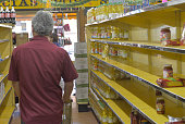 A shopper walks past nearly empty shelves at a supermarket due to a long term shortage in Caracas Venezuela on January 13 2015 Sliding oil prices...