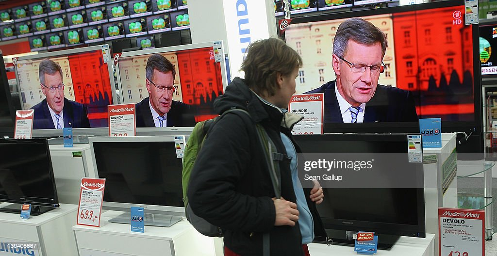 A shopper walks past television monitors showing an interview with German President Christian Wulff in which he was scheduled to respond to critics at an electronics store on January 4, 2011 in Berlin, Germany. Wulff has come under increasing pressure to resign following reports that he personally intervened in attempts to prevent journalists from writing about aspects of his personal life, including a recent call to Editor-in-Chief Kai Diekmann of Bild Zeitung, in which he threatened Diekmann with legal action should the paper publish a story about Wulff's personal finance conduct while Wulff was prime minister of Lower Saxony. These accusations come on the heels of revelations of cozy relationships between Wulff and businessmen in Lower Saxony that included free holidays and low interest loans.