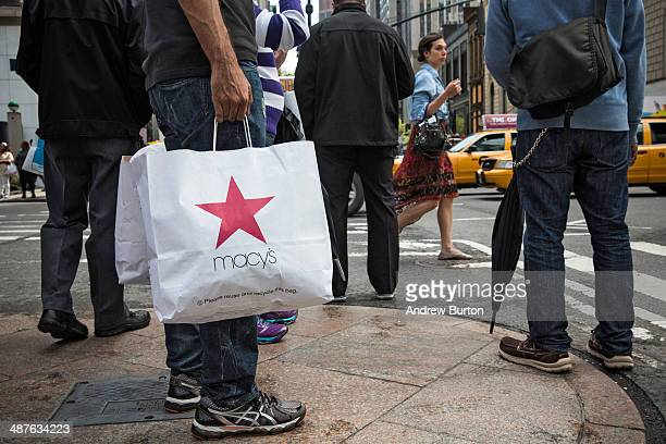 A shopper walks through Herald Square outside Macy's on 34th Street on May 1 2014 in New York City Consumer spending rose sharply in the month of...