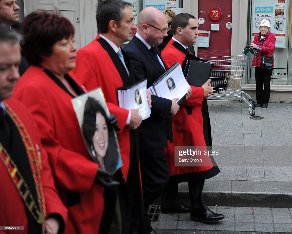 A shopper watches a procession led by Mayor of Drogheda Paul Bell on their way to the Memorial Service for murdered journalist Jill Meagher at St. Peter's Church on October 5, 2012 in Drogheda, Ireland. Mrs Meagher, 29, from County Louth was murdered after a night out in Melbourne, Australia, last month.