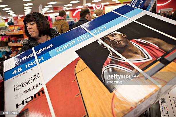 Shopper Wendy Hutton loads a 48inch television into a shopping cart at a Target Corp store ahead of Black Friday in Mentor Ohio US on Thursday Nov 27...