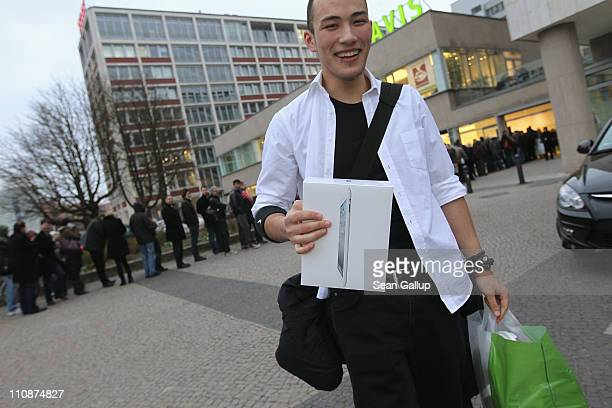 A shopper who had just bought the new Apple iPad 2 on the first day the tablet computer went on sale departs from a Gravis computer shop as others...