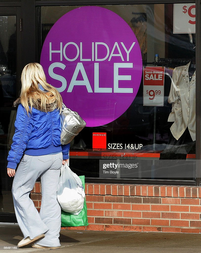 A shopper with her purchases passes 'Holiday Sale' signage in a store window December 27, 2005 in Mount Prospect, Illinois. Retailers are marking down prices as consumers are looking for post-Christmas deals.