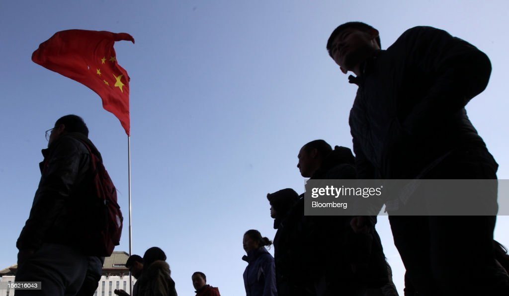 Shoppers and pedestrians walk past a Chinese national flag displayed outside a department store in Beijing, China, on Sunday, Nov. 11, 2012. China's retail sales exceeded forecasts and inflation unexpectedly cooled to the slowest pace in 33 months, signaling the government is boosting growth without driving a rebound in prices. Photographer: Tomohiro Ohsumi/Bloomberg via Getty Images