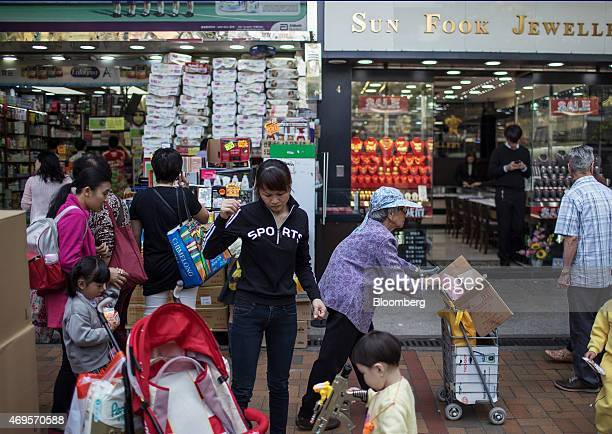 Shoppers and pedestrians walk past a pharmacy left and a jewelry store in the Sheung Shui district near the border with mainland China in Hong Kong...