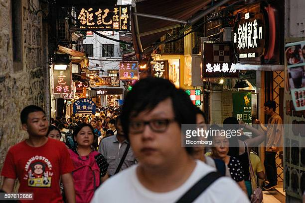 Shoppers and pedestrians walk past stores in Macau China on Sunday July 22 2016 Macau is scheduled to release gross domestic product figures on Aug...