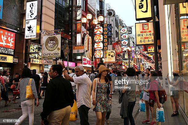Shoppers and pedestrians walk through the Dotonbori district of Osaka Japan on Wednesday June 24 2015Japanese consumer prices rose fractionally in...
