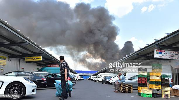 Shoppers and retailers are seen as smoke billows from a fire in a storage facility at the Dong Xuan shopping centre in Berlin's Lichtenberg district...