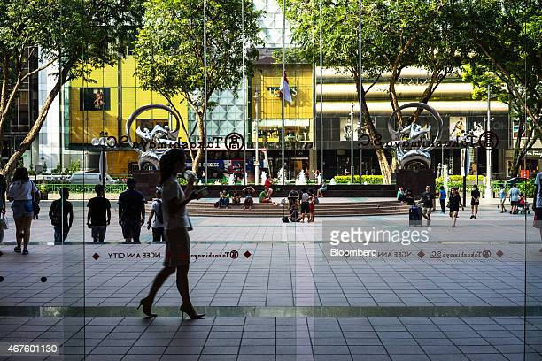 Shoppers and the Singapore national flag at halfmast are seen through glass doors of the Takashimaya department store on Orchard Road in Singapore on...