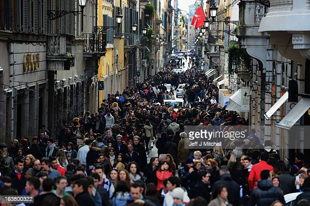 Shoppers and tourists crowd a street in one of the main shopping streets in Rome on March 16 2013 in Rome ItalyRome is preparing for the inauguration...