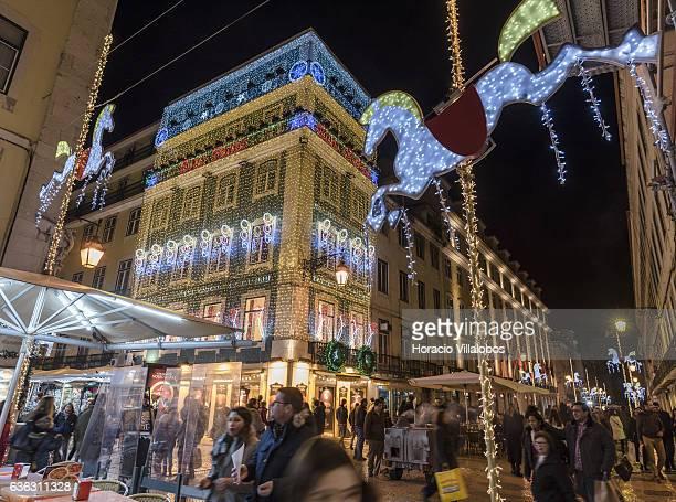 Shoppers and tourists walk through Rua Augusta beneath Christmas decorations on Casa Portuguesa do Pastel de Bacalhau days before Christmas and New...