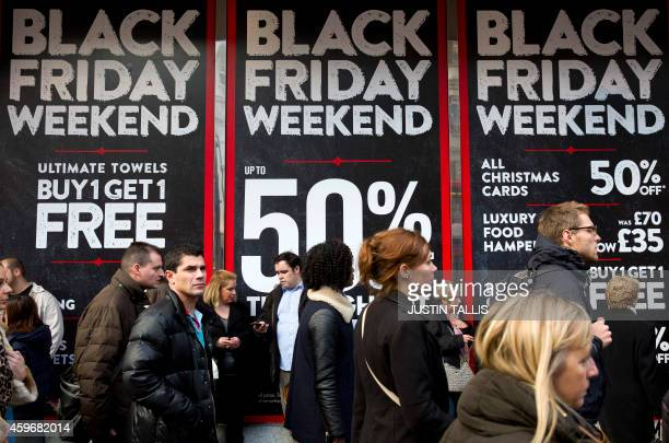 Shoppers are pictured walking past 'Black Friday' advertising in shop windows on Oxford Street in central London on November 28 2014 Police blasted...