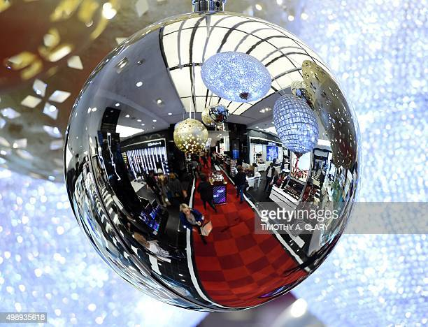 Shoppers are reflected in a Christmas decoration during Black Friday at Bloomingdale's Flagship store at 59th Street in New York City on November 27...