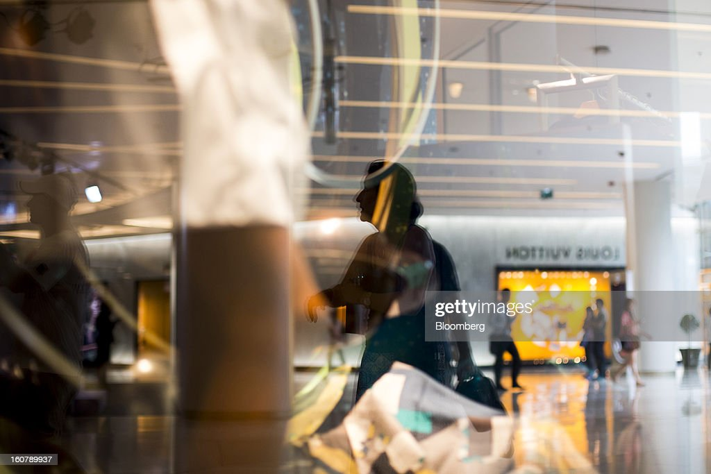 Shoppers are reflected in a store window display at the Siam Paragon shopping mall in Bangkok, Thailand, on Tuesday, Feb. 5, 2013. Thai inflation may average 2.8 percent this year, the Bank of Thailand said. Photographer: Brent Lewin/Bloomberg via Getty Images