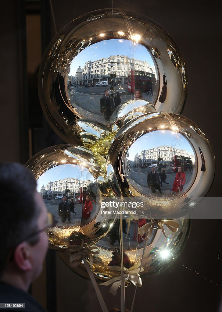 Shoppers are reflected in giant Christmas decorations in Regent Street on December 17, 2012 in London, England. Thousands of shoppers are expected in London's west end in the hunt for Christmas bargains in the next week.