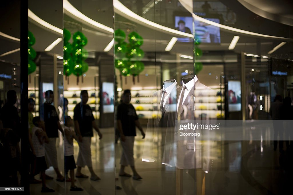 Shoppers are reflected in the window display of a Dolce & Gabbana Srl store at the Siam Paragon shopping mall in Bangkok, Thailand, on Tuesday, Feb. 5, 2013. Thai inflation may average 2.8 percent this year, the Bank of Thailand said. Photographer: Brent Lewin/Bloomberg via Getty Images