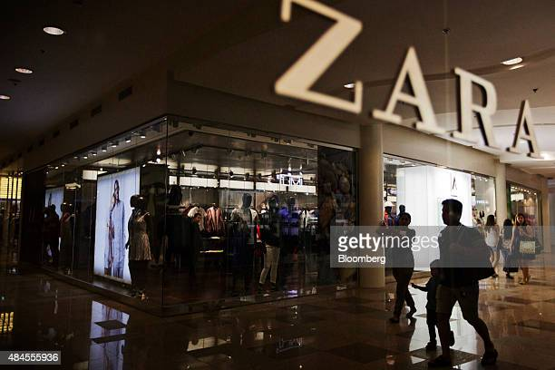Shoppers are reflected in the window of Zara fashion store operated by Inditex SA at the Ayala Center Cebu shopping mall operated by the Ayala...
