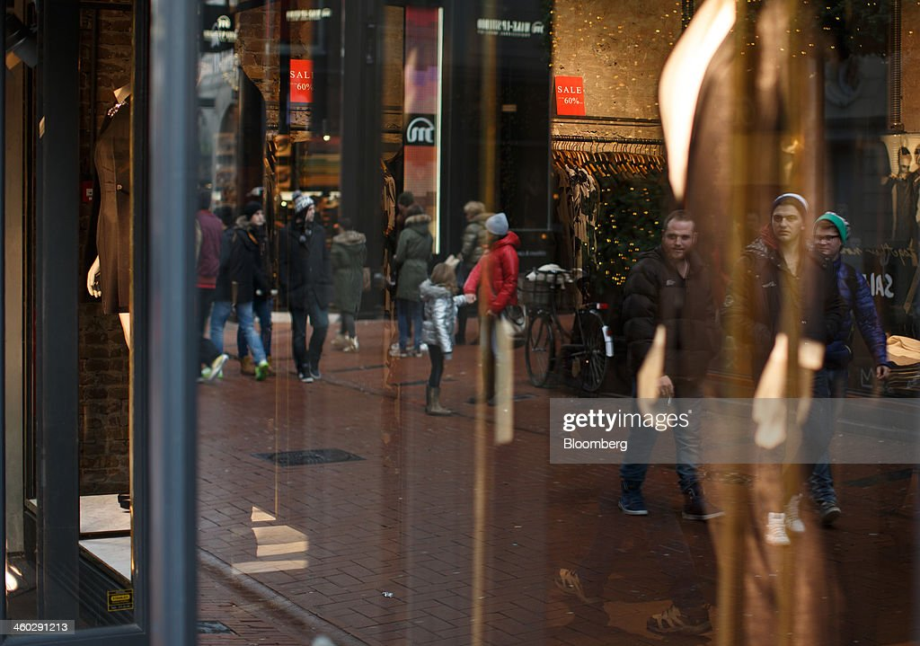 Shoppers are reflected in the windows of clothing fashion stores on a street in Amsterdam, Netherlands, on Thursday, Jan. 2, 2014. The Netherlands will grow by 0.5 percent in 2014 as the world economy improves and consumer confidence picks up, the country's central bank forecast Dec. 9. Photographer: Jasper Juinen/Bloomberg via Getty Images