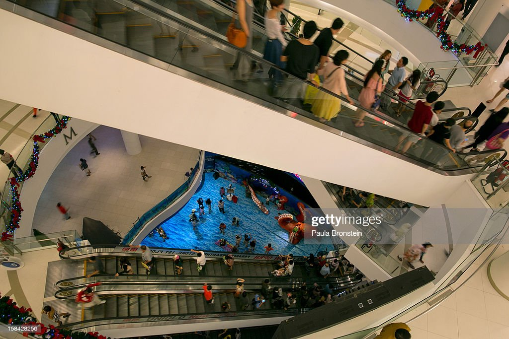 Shoppers are seen on an escalator inside the Paragon mall, one of the Bangkok's most popular shopping centers December 16, 2012 in Bangkok,Thailand.Thailand's high tourist season is booming this year compared to 2011 which was tainted by the flooding as Christmas shoppers visit the malls looking for the bargains.