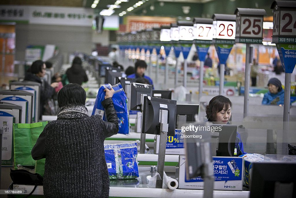 Shoppers are served by cashiers at check-out counters in Hanaro Mart in Seoul, South Korea, on Tuesday, Feb. 26, 2013. South Korean consumer confidence remained at its highest level since May as gains in the won drove down the prices of imported goods. Photographer: Jean Chung/Bloomberg via Getty Images