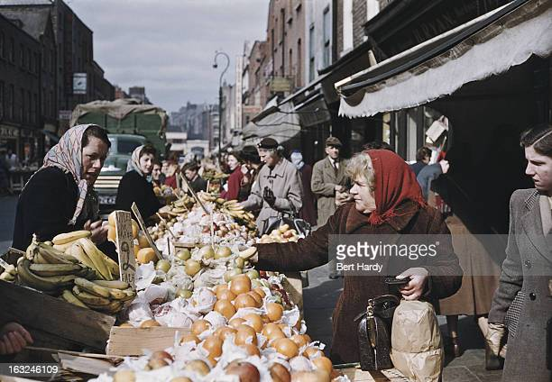 Shoppers at a fruit stall on a street in Dublin Eire June 1955 Original publication Picture Post 7808 Dublin pub 18th June 1955