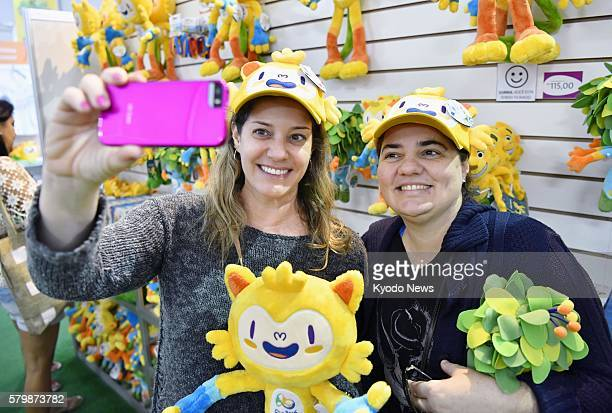 Shoppers at a megastore in Rio de Janeiro that sells official products for the 2016 Olympic and Paralympic Games wear hats in the shape of Vinicius...
