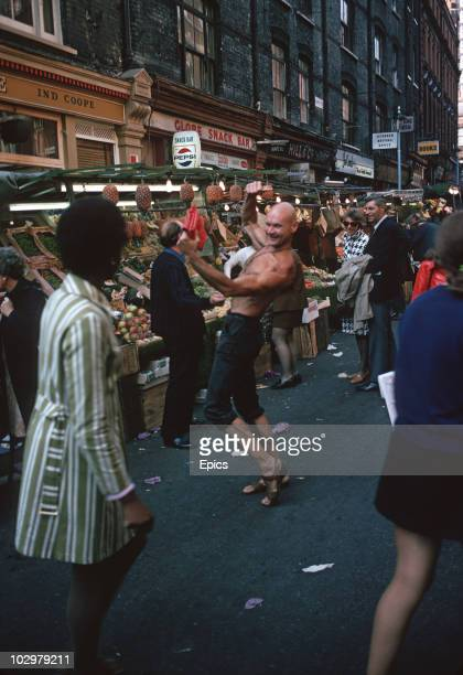 Shoppers at Berwick Street fruit and vegetable market Soho stop to admire one of the local characters October 1970