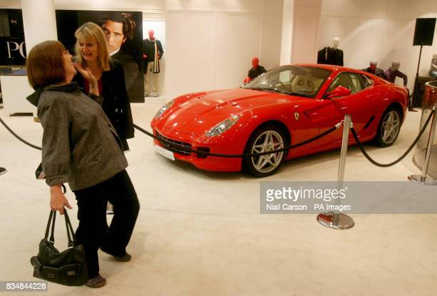 Shoppers at the Brown Thomas department store in Dublin view expensive sports cars on the day Finance Minister Brian Lenihan announces his Budget for...