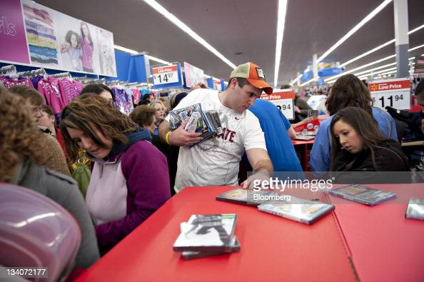 Shoppers browse $196 DVD movies at a Black Friday sale at a WalMart Stores Inc store in Mentor Ohio US on Thursday Nov 24 2011 Retailers are pouring...