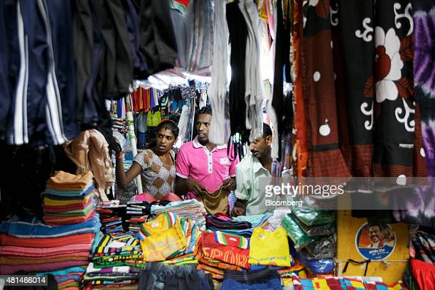 Shoppers browse at a garment stall in a market in the Pettah area of Colombo Sri Lanka on Sunday July 19 2015 The International Monetary Fund in May...