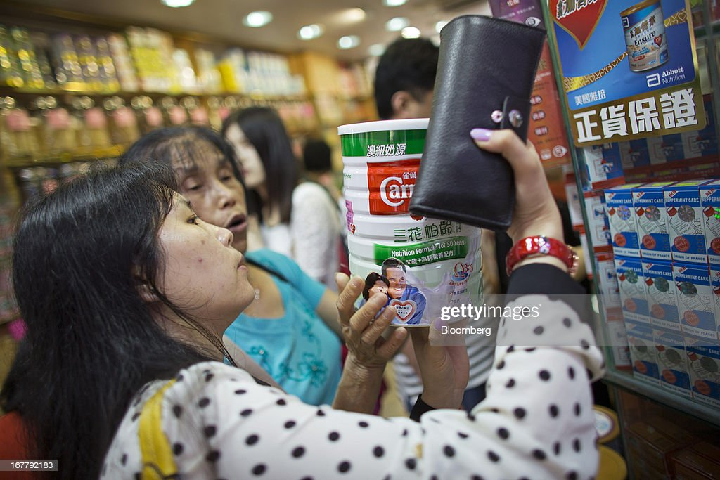 Shoppers browse cans of baby formula displayed in a pharmacy in the Mongkok district of Hong Kong, China, on Tuesday, April 30, 2013. Financial Secretary John Tsang on Feb. 27 projected annual growth of 1.5 percent to 3.5 percent this year following 2012's 1.4 percent, the weakest rate since 2009 as Europe's sovereign debt crisis sapped global demand. Photographer: Lam Yik Fei/Bloomberg via Getty Images