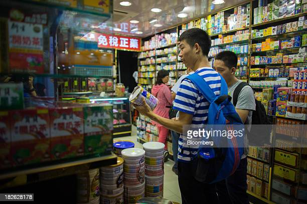 Shoppers browse cans of baby formula displayed in a pharmacy in the Mong Kok area of Hong Kong China on Tuesday Oct 1 2013 China's 'Golden Week'...