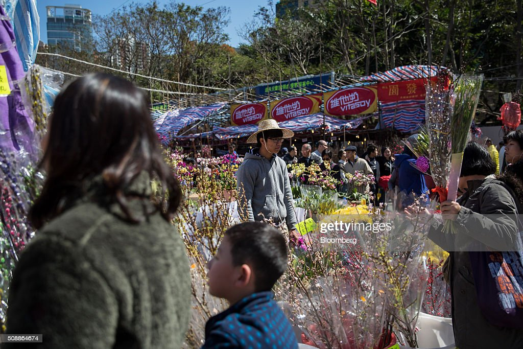 Shoppers browse flowers displayed for sale for the Lunar New Year at a flower market in Victoria Park in Hong Kong, China, on Sunday, Feb 7, 2016. The city's financial markets will close on Feb. 8 for the Lunar New Year holidays and resume trading on Feb. 11. Photographer: Billy H.C. Kwok/Bloomberg via Getty Images
