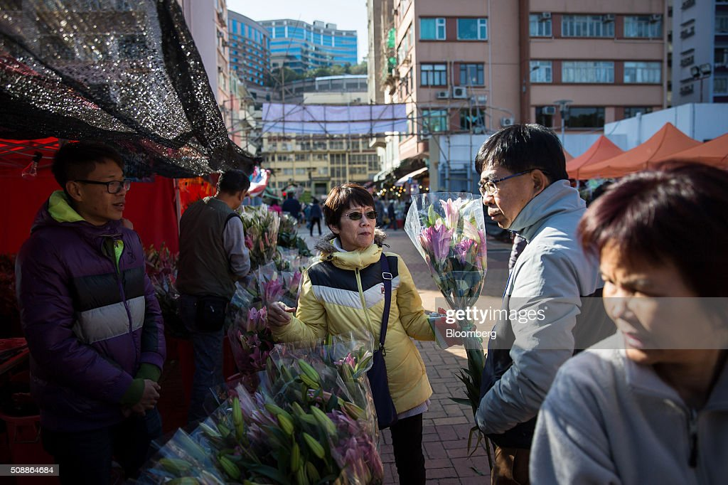 Shoppers browse flowers displayed for sale for the Lunar New Year at a flower market in the Mong Kok district of Hong Kong, China, on Sunday, Feb 7, 2016. The city's financial markets will close on Feb. 8 for the Lunar New Year holidays and resume trading on Feb. 11. Photographer: Billy H.C. Kwok/Bloomberg via Getty Images