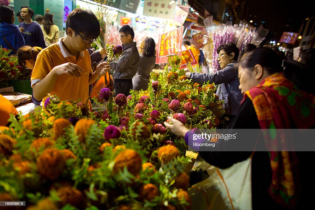 Shoppers browse flowers displayed for sale for the Lunar New Year in the Mongkok district of Hong Kong, China, on Thursday, Feb. 7, 2013. Hong Kong's stock market will be shut for three days next week for the Lunar New Year holidays, while markets in mainland China will be closed for the whole week. Photographer: Lam Yik Fei/Bloomberg via Getty Images