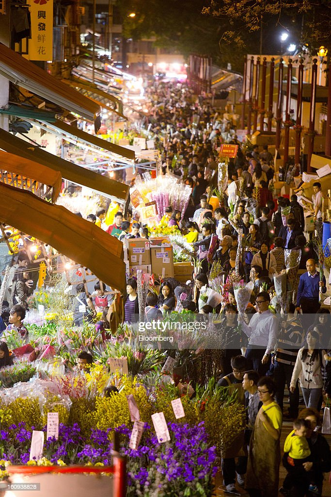 Shoppers browse flowers displayed for sale for the Lunar New Year on Flower Market Road in the shopping district of Mongkok in Hong Kong, China, on Thursday, Feb. 7, 2013. Hong Kong's stock market will be shut for three days next week for the Lunar New Year holidays, while markets in mainland China will be closed for the whole week. Photographer: Lam Yik Fei/Bloomberg via Getty Images