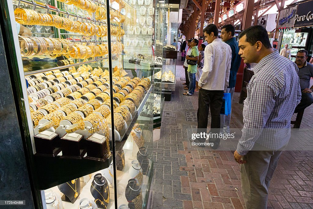 Shoppers browse gold jewelry for sale in the Dubai Gold Souk in the Deira district of Dubai, United Arab Emirates, on Tuesday, July 2, 2013. Gold swung between gains and losses in London as investors weighed prospects for increased physical demand against a slowing stimulus in the U.S. Photographer: Duncan Chard/Bloomberg via Getty Images