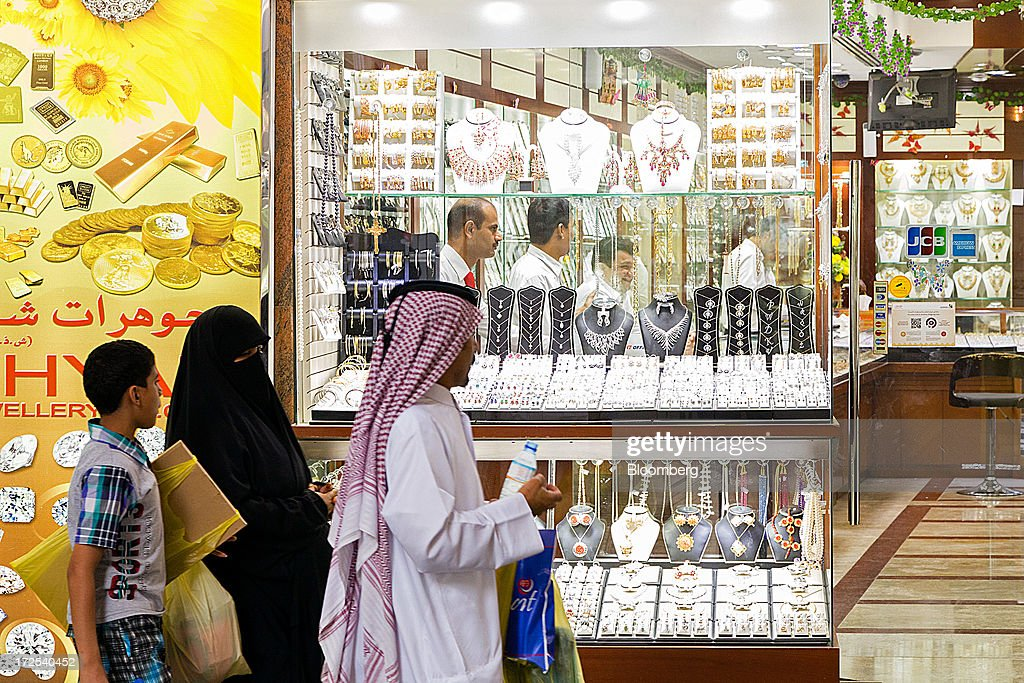 Shoppers browse gold jewelry on display in the windows of a gold store in the Dubai Gold Souk in the Deira district of Dubai, United Arab Emirates, on Tuesday, July 2, 2013. Gold swung between gains and losses in London as investors weighed prospects for increased physical demand against a slowing stimulus in the U.S. Photographer: Duncan Chard/Bloomberg via Getty Images