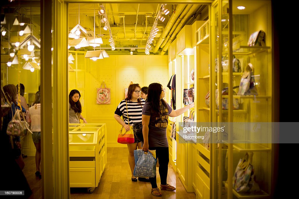 Shoppers browse handbags inside a store at the Siam Center shopping mall in Bangkok, Thailand, on Tuesday, Feb. 5, 2013. Thai inflation may average 2.8 percent this year, the Bank of Thailand said. Photographer: Brent Lewin/Bloomberg via Getty Images