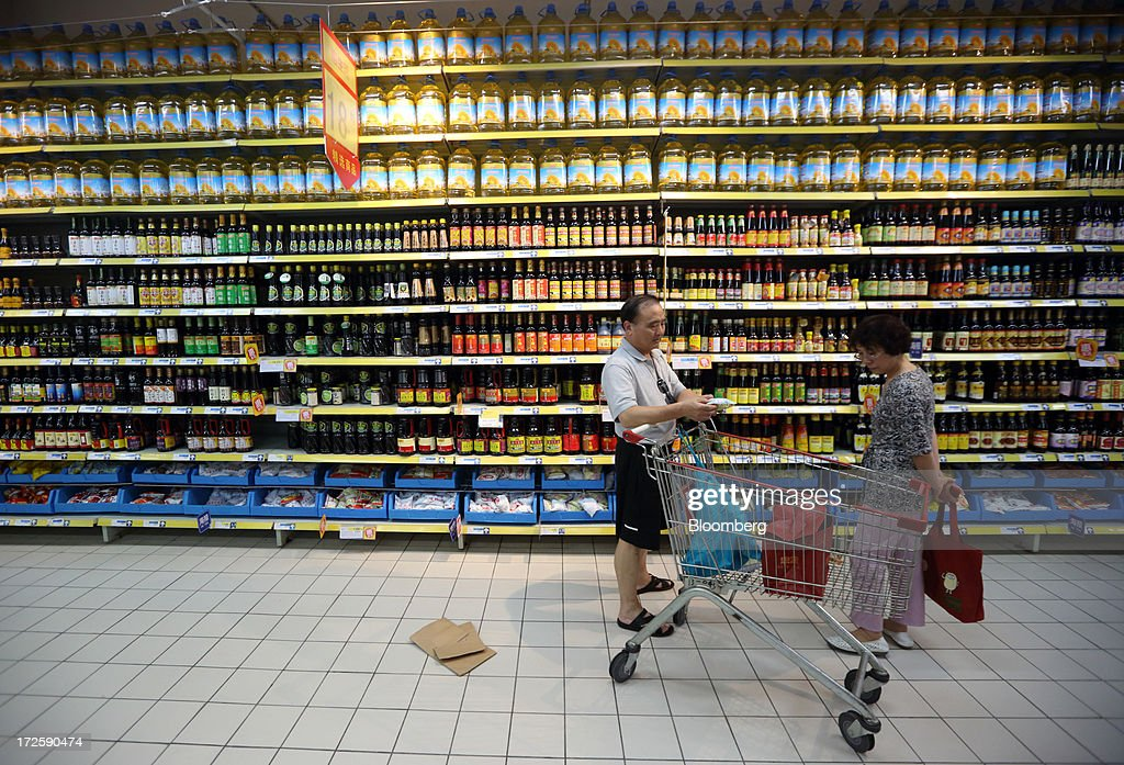 Shoppers browse in front of bottles of oil displayed at a store in Shanghai, China, on Tuesday, July 2, 2013. Banks including Goldman Sachs Group Inc. have pared their growth projections for China this year to 7.4 percent, below the government's 7.5 percent goal disclosed at the March conference at which Li Keqiang became premier. Photographer: Tomohiro Ohsumi/Bloomberg via Getty Images