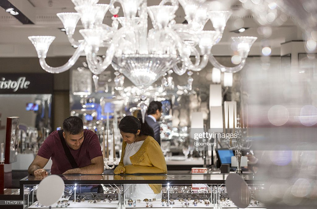 Shoppers browse jewelry displayed on a counter underneath chandeliers at Harrods luxury department store in London, U.K., on Monday, June 24, 2013. Harrods, which has more than 1 million square feet (90,000 square meters) of selling space, isn't concerned about the outlook for spending on luxury goods, Harrods Managing Director Michael Ward said. Photographer: Jason Alden/Bloomberg via Getty Images